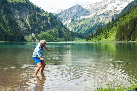 Mature man skipping stones at Lake Vilsalpsee, Tannheim Valley, Austria Stock Photo - Premium Royalty-Free, Code: 600-06841889