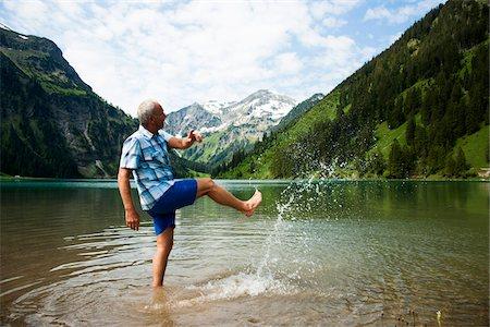 Mature man standing in lake, kicking water, Lake Vilsalpsee, Tannheim Valley, Austria Stock Photo - Premium Royalty-Free, Code: 600-06841894