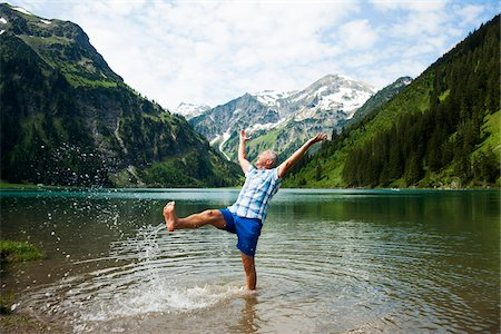Mature man standing in lake, kicking water, Lake Vilsalpsee, Tannheim Valley, Austria Stock Photo - Premium Royalty-Free, Code: 600-06841895