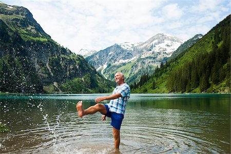 Mature man standing in lake, kicking water, Lake Vilsalpsee, Tannheim Valley, Austria Stock Photo - Premium Royalty-Free, Code: 600-06841896