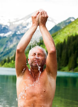 Close-up of Mature man standing in lake, splashing water on face, Lake Vilsalpsee, Tannheim Valley, Austria Stock Photo - Premium Royalty-Free, Code: 600-06841897