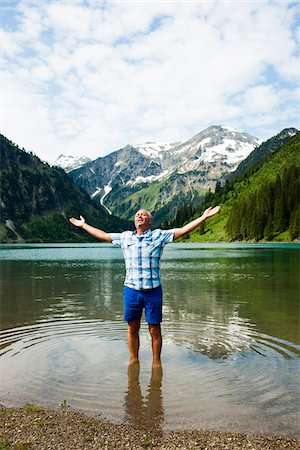 Mature man with arms stretched outward, standing in Lake Vilsalpsee, Tannheim Valley, Austria Stock Photo - Premium Royalty-Free, Code: 600-06841891
