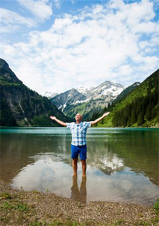 Mature man with arms stretched outward, standing in Lake Vilsalpsee, Tannheim Valley, Austria Stock Photo - Premium Royalty-Free, Code: 600-06841892