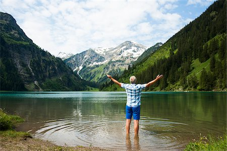 Backview of mature man with arms stretched outward, standing in Lake Vilsalpsee, Tannheim Valley, Austria Stock Photo - Premium Royalty-Free, Code: 600-06841893