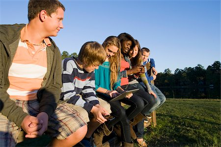 Group of pre-teens sitting on fence, looking at tablet computer and cellphones, outdoors, Florida, USA Stock Photo - Premium Royalty-Free, Code: 600-06841924