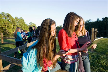 Group of pre-teens sitting on fence, looking at tablet computers and cellphones, outdoors, Florida, USA Stock Photo - Premium Royalty-Free, Code: 600-06841922