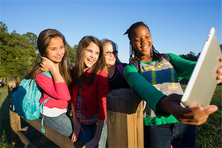 Pre-teen girls standing outdoors, looking at tablet computer laughing, Florida, USA Stock Photo - Premium Royalty-Free, Code: 600-06841923