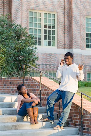 Young man and young woman outdoors on college campus steps, young man using smartphone, Florida, USA Stock Photo - Premium Royalty-Free, Code: 600-06841938