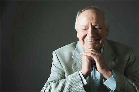 Portrait of senior man smiling with eyes closed, studio shot on grey background Stock Photo - Premium Royalty-Free, Code: 600-06841956