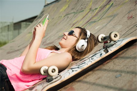 Teenage Girl Listening to MP3 Player in Skatepark, Feudenheim, Mannheim, Baden-Wurttemberg, Germany Stock Photo - Premium Royalty-Free, Code: 600-06894841