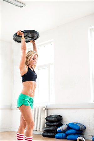Woman Lifting Weight over her Head in Fitness Studio, Copenhagen, Denmark Stock Photo - Premium Royalty-Free, Code: 600-06895030