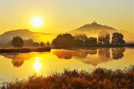 Wachsenburg Castle with Morning Mist and Sun reflecting in Lake at Dawn, Drei Gleichen, Thuringia, Germany Stock Photo - Premium Royalty-Free, Code: 600-06899715
