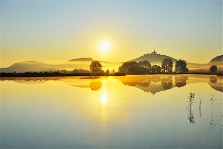 Wachsenburg Castle with Morning Mist and Sun reflecting in Lake at Dawn, Drei Gleichen, Thuringia, Germany Stock Photo - Premium Royalty-Free, Code: 600-06899716