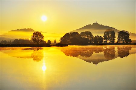Wachsenburg Castle with Morning Mist and Sun reflecting in Lake at Dawn, Drei Gleichen, Thuringia, Germany Stock Photo - Premium Royalty-Free, Code: 600-06899717