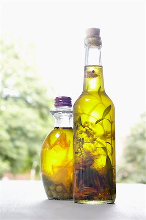 Still life of bottles of olive oil with herbs on window sill, Germany Stock Photo - Premium Royalty-Free, Code: 600-06899766