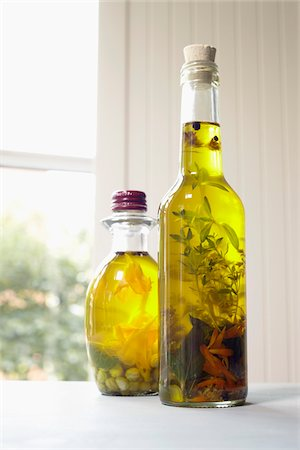 Still life of bottles of olive oil with herbs on window sill, Germany Stock Photo - Premium Royalty-Free, Code: 600-06899769