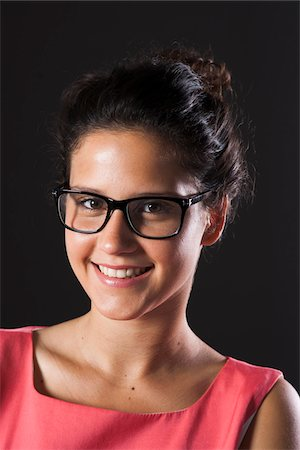 Portrait of teenage girl wearing horn-rimmed eyeglasses, smiling and looking at camera Stock Photo - Premium Royalty-Free, Code: 600-06899814