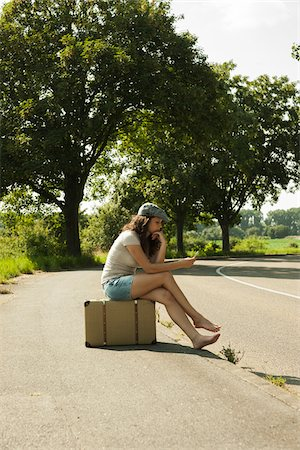 Teenaged girl sitting on suitcase on the side of the road, looking at cell phone, in summer, Germany Stock Photo - Premium Royalty-Free, Code: 600-06899824