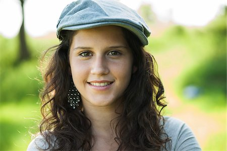 female only - Close-up portrait of teenaged girl wearing cap outdoors, smiling and looking at camera, Germany Stock Photo - Premium Royalty-Free, Code: 600-06899825