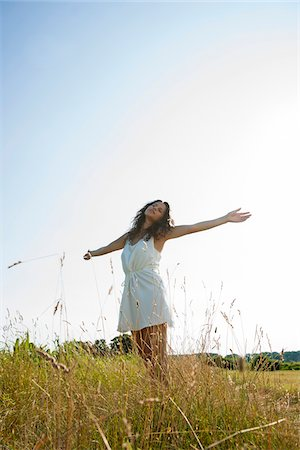 Teenaged girl standing in field with arms outstretched, Germany Stock Photo - Premium Royalty-Free, Code: 600-06899842