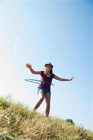 preteen  smile  one  alone - Girl using hula-hoop outdoors on hill, Germany Stock Photo - Premium Royalty-Free, Code: 600-06899855