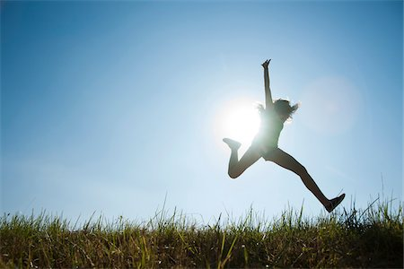 Silhouette of teenaged girl jumping in air across field, Germany Stock Photo - Premium Royalty-Free, Code: 600-06899859
