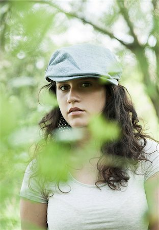 Close-up portrait of teenaged girl wearing cap outdoors, looking at camera through leaves, Germany Stock Photo - Premium Royalty-Free, Code: 600-06899851