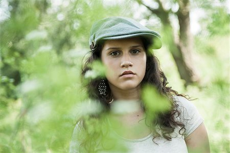 Close-up portrait of teenaged girl wearing cap outdoors, looking at camera through leaves, Germany Stock Photo - Premium Royalty-Free, Code: 600-06899852