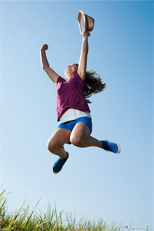 Girl holding hat, jumping in mid-air over field, Germany Stock Photo - Premium Royalty-Free, Code: 600-06899864