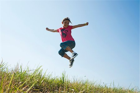 Girl jumping in mid-air over field, Germany Stock Photo - Premium Royalty-Free, Code: 600-06899865