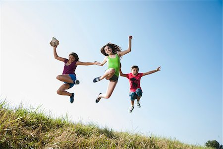 diversión - Girls jumping in mid-air over field, Germany Foto de stock - Sin royalties Premium, Código: 600-06899866