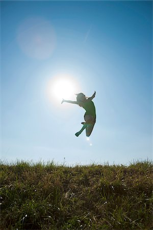 Silhouette of Teenaged girl jumping in mid-air over field, Germany Stock Photo - Premium Royalty-Free, Code: 600-06899861