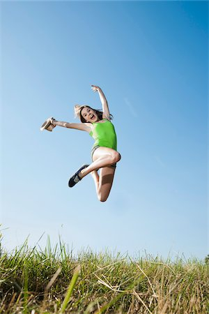 Teenaged girl jumping in mid-air over field, Germany Stock Photo - Premium Royalty-Free, Code: 600-06899862