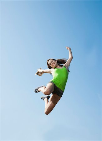 Teenaged girl jumping in mid-air against blue sky, Germany Stock Photo - Premium Royalty-Free, Code: 600-06899863