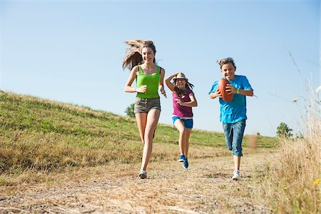 Girls running along pathway in field, Germany Stock Photo - Premium Royalty-Free, Code: 600-06899875