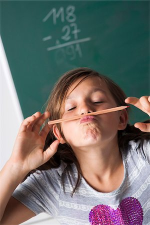 preteen girl pigtails - Portrait of girl standing in front of blackboard in classroom, holding pencil over mouth, Germany Stock Photo - Premium Royalty-Free, Code: 600-06899884