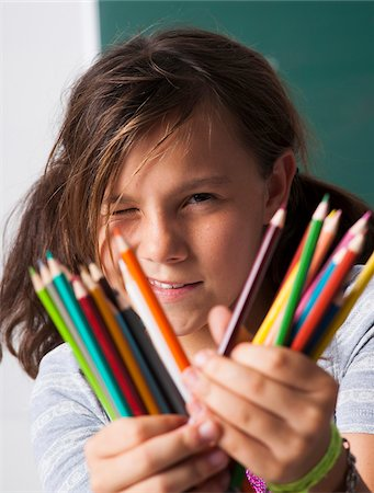 preteen girl pigtails - Close-up of girl holding colored pencils in hands, Germany Stock Photo - Premium Royalty-Free, Code: 600-06899885