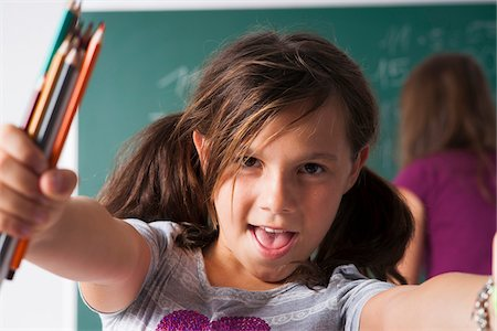 preteen girl pigtails - Close-up portrait of girl in classroom, holding colored pencils in hands, Germany Stock Photo - Premium Royalty-Free, Code: 600-06899886