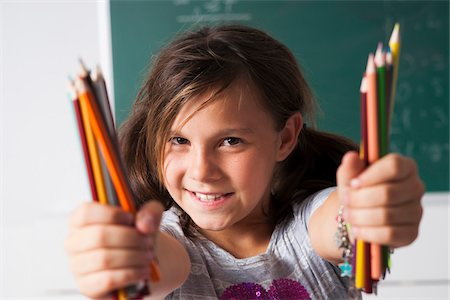 preteen girl pigtails - Close-up portrait of girl holding colored pencils in hands, Germany Stock Photo - Premium Royalty-Free, Code: 600-06899887