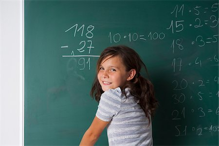 Girl standing in classroom in front of blackboard dong mathematical questions, Germany Stock Photo - Premium Royalty-Free, Code: 600-06899888