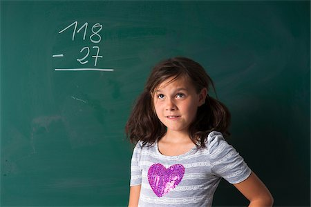 Portrait of girl standing in front of blackboard in classroom, Germany Stock Photo - Premium Royalty-Free, Code: 600-06899880