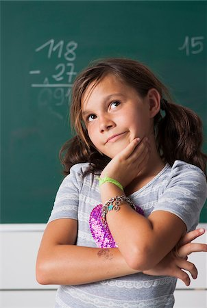 Portrait of girl standing in front of blackboard in classroom, Germany Stock Photo - Premium Royalty-Free, Code: 600-06899881