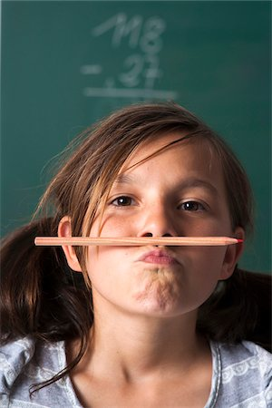 Portrait of girl standing in front of blackboard in classroom, holding pencil with mouth, Germany Stock Photo - Premium Royalty-Free, Code: 600-06899882