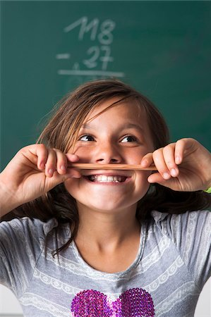Portrait of girl standing in front of blackboard in classroom, holding pencil over mouth, Germany Stock Photo - Premium Royalty-Free, Code: 600-06899883