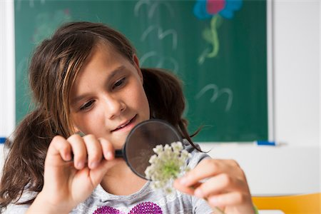 preteen girl pigtails - Girl in classroom examining flower with magnifying glass, Germany Stock Photo - Premium Royalty-Free, Code: 600-06899895