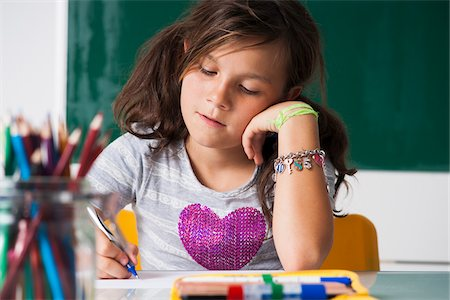 preteen girl pigtails - Girl sitting at desk in classroom, Germany Stock Photo - Premium Royalty-Free, Code: 600-06899892