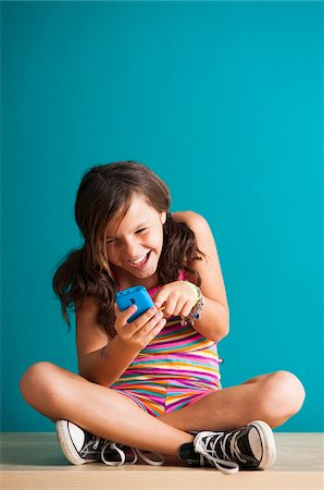 preteen girl pigtails - Girl sitting on floor looking at smartphone, Germany Stock Photo - Premium Royalty-Free, Code: 600-06899904