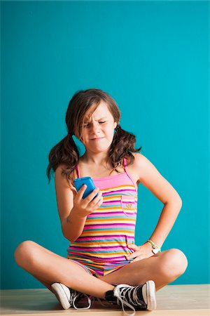 preteen girl pigtails - Girl sitting on floor looking at smartphone, Germany Stock Photo - Premium Royalty-Free, Code: 600-06899905