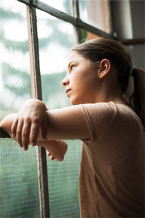 Girl looking out of window, Germany Stock Photo - Premium Royalty-Free, Code: 600-06899908