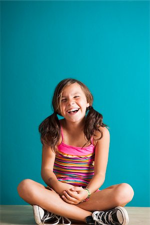 preteen girl pigtails - Portrait of girl sitting on floor, laughing, Germany Stock Photo - Premium Royalty-Free, Code: 600-06899900